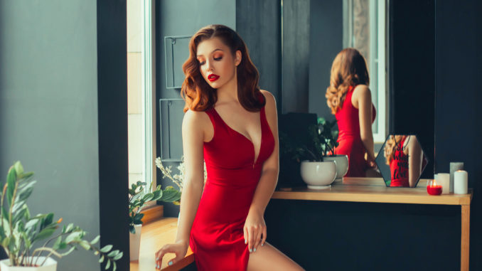 Hot young adult, proud and domineering woman dressed in a long scarlet red long dress