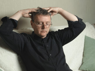 A man with glasses and a black shirt is massaging his head.