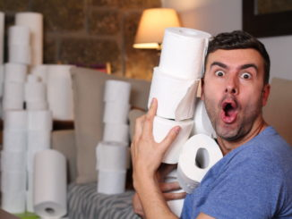 Man stocking up toilet paper at home.