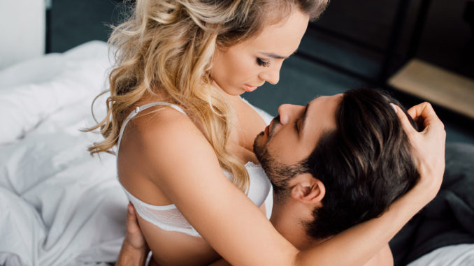 Passionate women touching hair of muscular men on bed