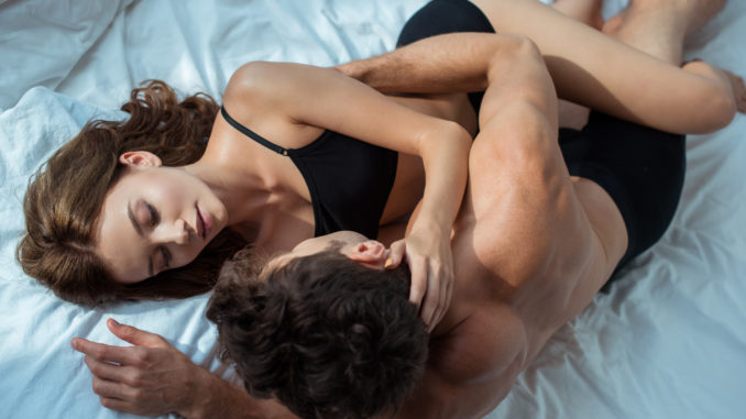 Top view of men and women hugging while lying on bed