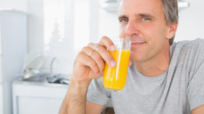 Happy man drinking orange juice in kitchen looking at camera