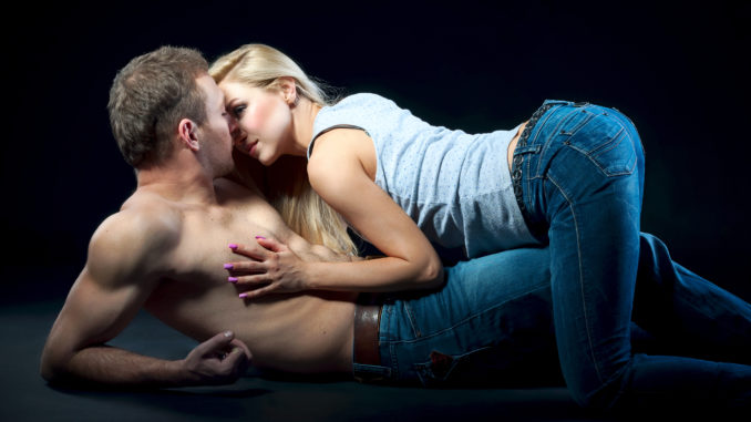 Young couple lying on the floor. Woman on top men put a hand on his chest.
