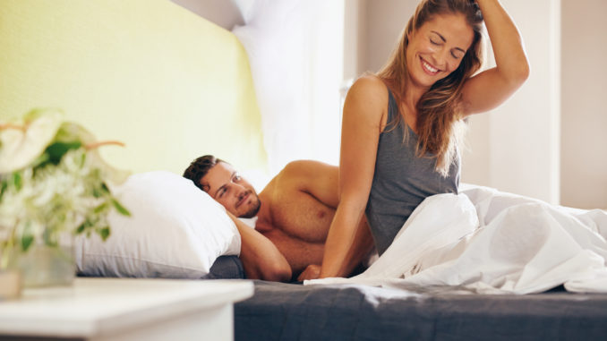 Happy young couple waking up in the morning on bed.
