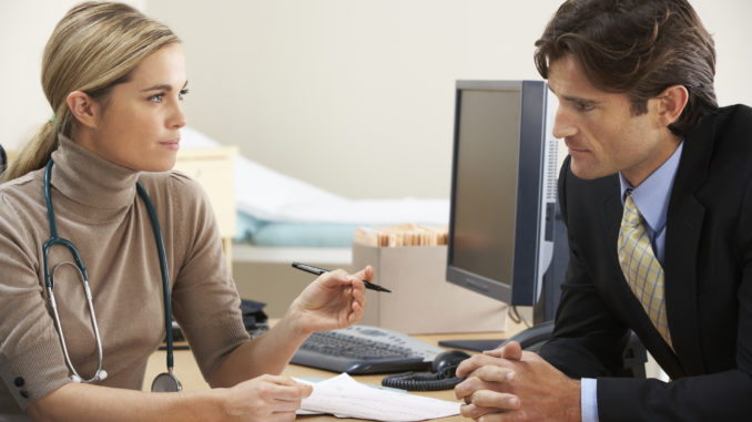 Female Doctor talking to businessman patient