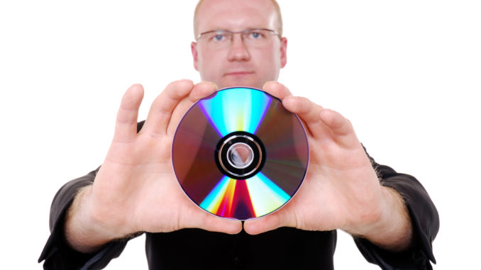 A man holding a CD on an isolated white background.