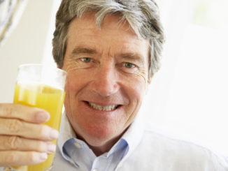 Senior Man Smiling At Camera And Drinking Orange Juice