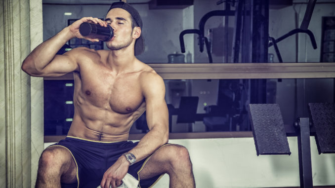 Attractive athletic shirtless young man drinking protein shake from blender in gym