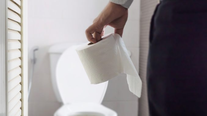 Man holding tissue paper standing next to toilet bowl - health problem concept