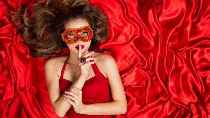 Woman in Venetian Mask Lying on Red Silk Fabric Background, Fashion Model Carnival Secret, Finger on Lips