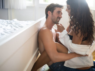 Romantic young couple being intimate in bedroom