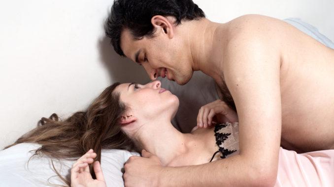 Happy young attractive happy couple in bedroom