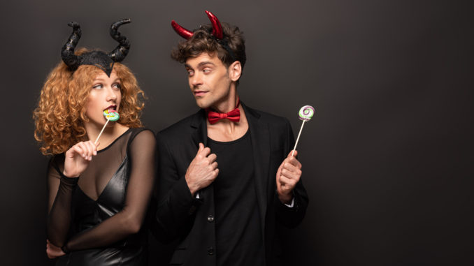 Beautiful couple posing in halloween costumes with sweet lollipops on black