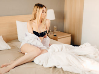 Young blonde woman sitting on unmade bed, looking really with shirt down on her bare shoulder.
