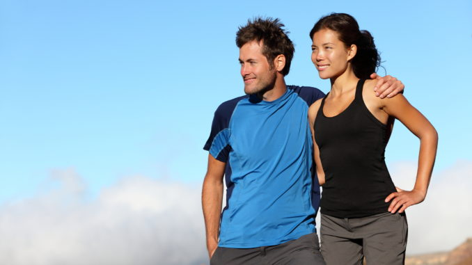Happy multiracial couple looking outdoors. Sporty healthy young interracial couple looking at blue sky smiling. Asian woman and man.