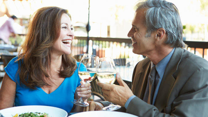 Mature Couple Enjoying Meal At Outdoor Restaurant smiling at each other