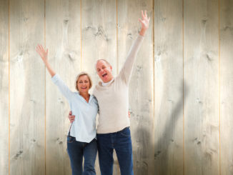 Happy mature couple cheering at camera against pale wooden planks