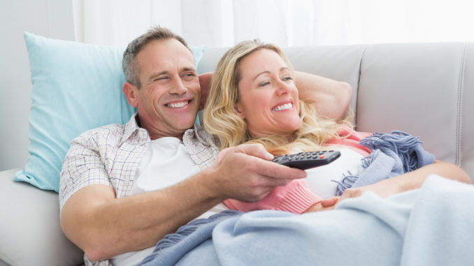 Happy couple cuddling on the couch watching television at home in the living room