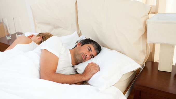 Sad couple lying in the bed after having an argument