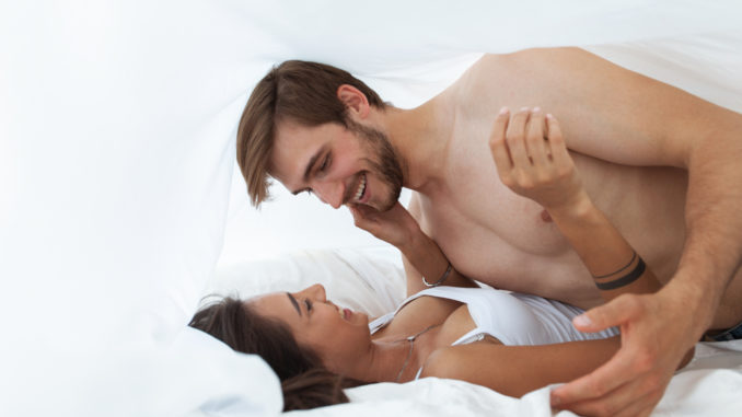 Intimate young couple in bedroom enjoying each other