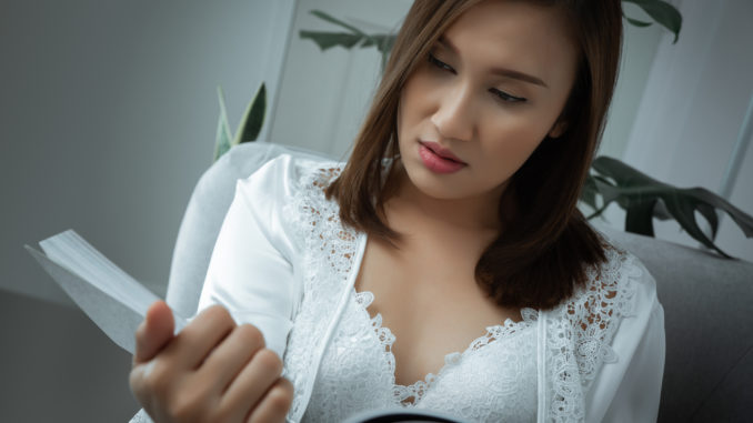 Woman wear silk nightwear addicted to reading novels at night