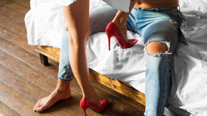 Woman seducing her men by wearing red high heel shoes in bedroom