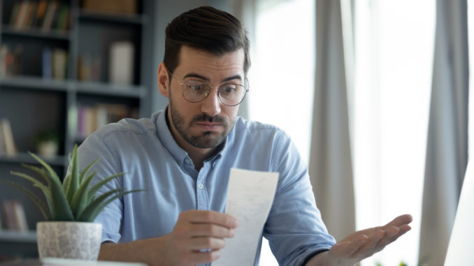 Confused shocked man wearing glasses looking at receipt