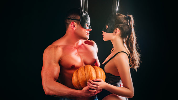 Halloween sensual couple. models each other with Pumpkin in halloween bunny mask. Design for banner. Boyfriend and girlfriend gently touch, fashion men and woman, boy girl young lovers
