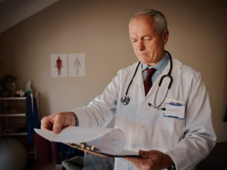 Senior male doctor holding clipboard checking reports in hospital
