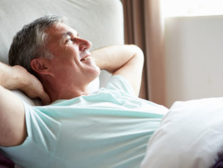 Middle Aged Man Waking Up In Bed Looking Away From Camera Smiling