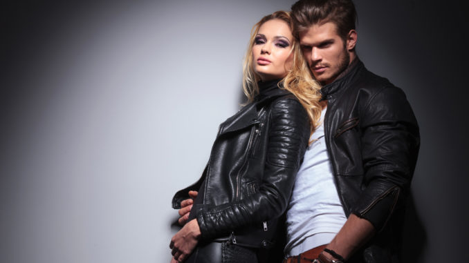 Hot fashion women leaning on her lover while he is looking away from the camera.