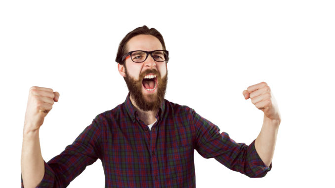 Handsome hipster cheering on white background