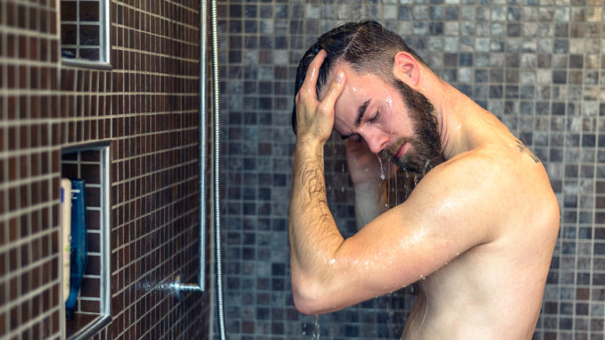 Young man with a beard standing washing his hair in the shower with shampoo rinsing it off under the jet of water, upper body with tattoo