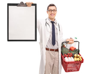 Young doctor holding a shopping basket full of groceries and a clipboard isolated on white background