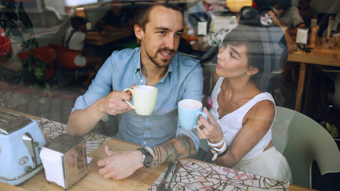 Man talking to women with cup of cappuccino while resting in cafe