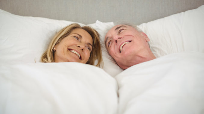 Happy senior couple lying on bed in bedroom