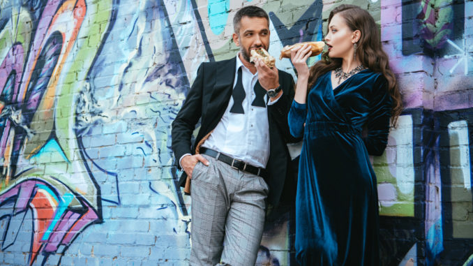 couple in luxury clothing eating hot dogs near wall with graffiti on street