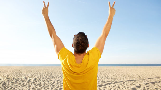 Portrait from back of man cheering with hands raised at the beach