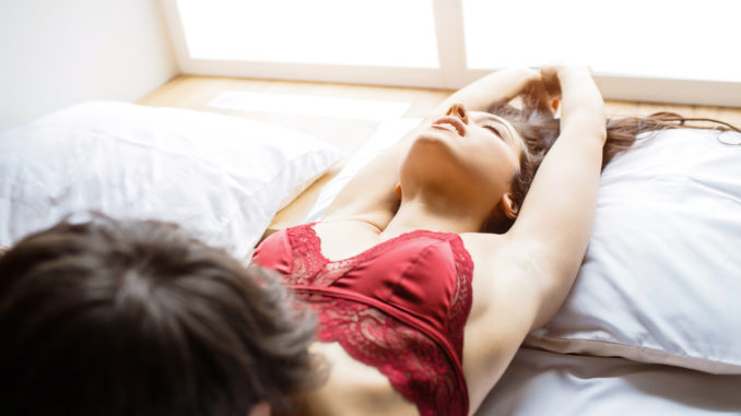 Young couple have intimacy on bed.