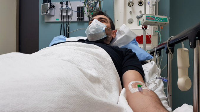 Young man lying in hospital bed.