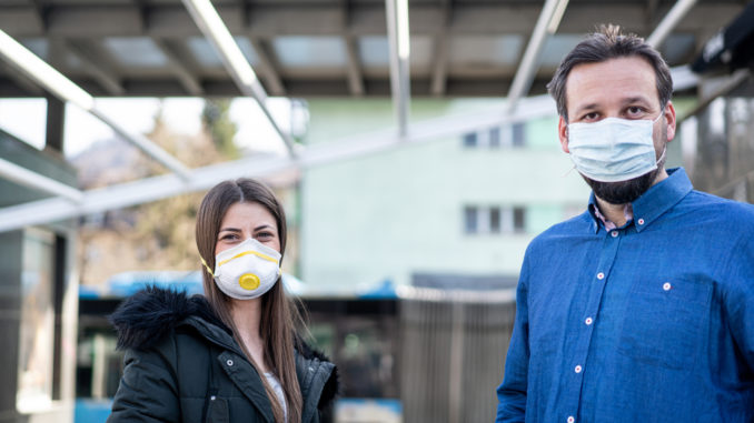 Couple on street with mask against virus pollution