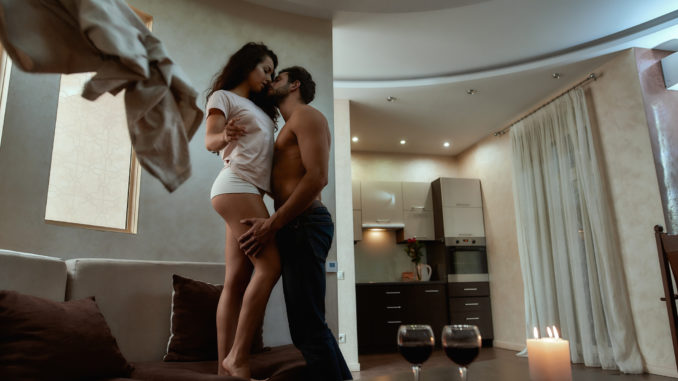 Young men and women undressing each other during sexual foreplay at home.