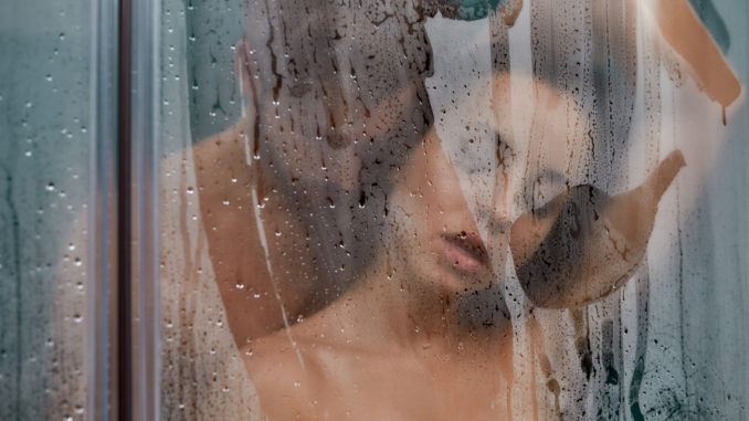 Selective focus of men kissing women while relaxing together taking shower in the morning