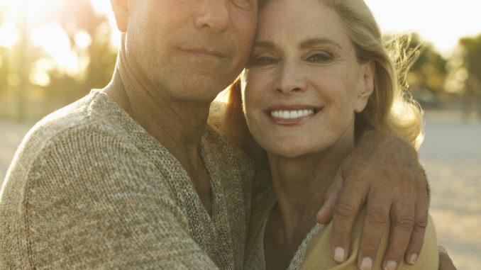 Closeup portrait of happy senior couple embracing on tropical beach