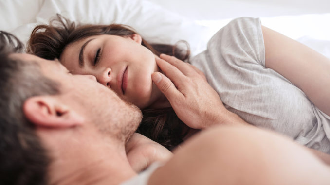 Young women lying on bed with man. Romantic young couple on bed.
