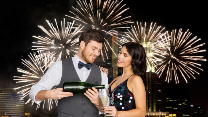 Celebration and holidays concept - happy couple with bottle of non alcoholic champagne and wine glass at party over firework lights at night city background