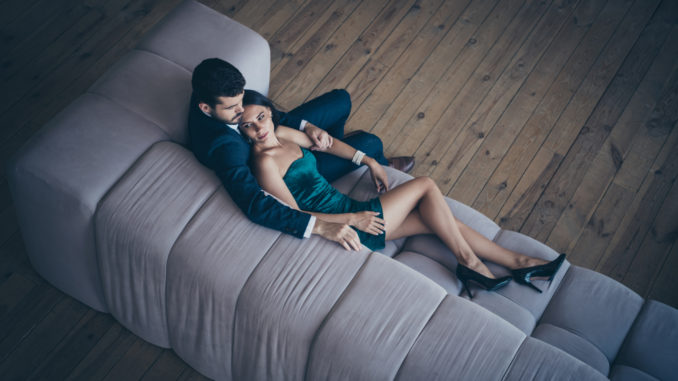High angle above view photo of two style stylish trendy classy people, couple rich guy and lady lying close on comfy couch night club party look wear formalwear suit short shiny dress loft indoors