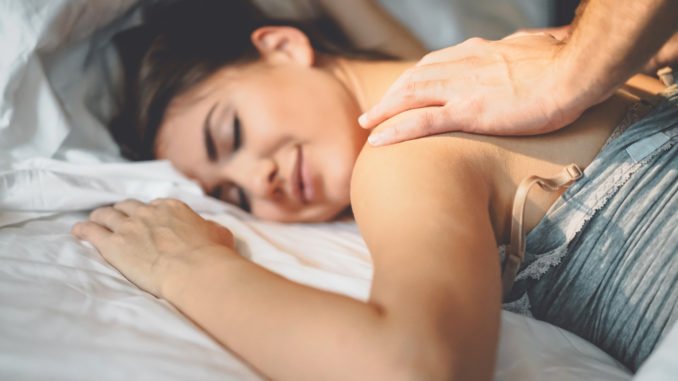 Happy couple having tender moments in the bed - Young romantic lovers intimate massaging and cuddling in the bedroom - People love relationship and relax wellness treatment concept