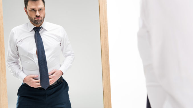 Dissatisfied chubby man in formal wear looking at mirror on white with copy space
