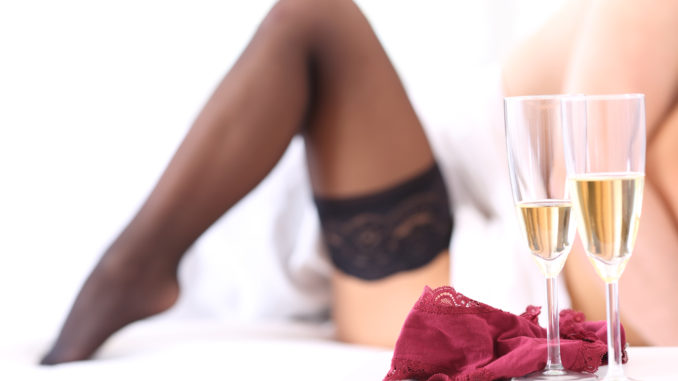 Unfocused couple having sex on a bed after a celebration with champagne cups in foreground